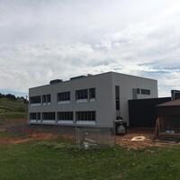 On voit un bâtiment entouré d'une clôture de construction. Il s'agit du nouveau campus du cégep des Îles-de-la-Madeleine.