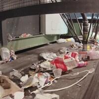 On voit un robot trieur à l'oeuvre sur un convoi de matières recyclables.