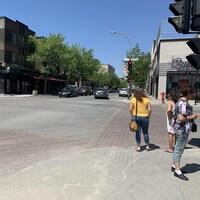Des personnes attendent de traverser sur un coin de rue du centre-ville.