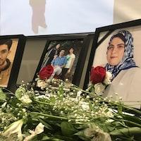 Des roses et des fleurs blanches devant des cadres ornés de rubans noirs.