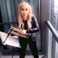Photo d'une femme aux cheveux blonds qui tient une chaise pliante dans les mains.