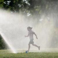La jeune fille court sous un jet d'eau dans un parc.