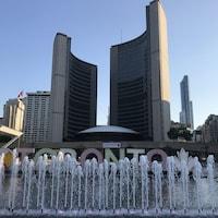 Hôtel de Ville de Toronto, la fontaine devant avec écrit en grosses lettres derrière les jets d'eau : TORONTO