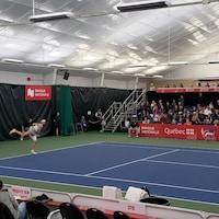 Une joueuse de tennis termine son service devant une foule.