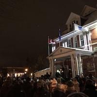Des gens rassemblés à la nuit tombée, devant un bâtiment municipal