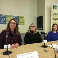 Trois femmes assises derrière une table avec des micros donnent une conférence de presse sur la violence conjugale en milieu de travail.