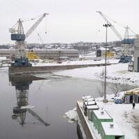 Une vue d'ensemble du chantier naval québécois Davie, en hiver, lors d'une journée grise. On y voit des grues et un travailleur qui marche près du fleuve.