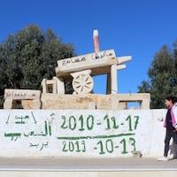 Une jeune fille tirant un valise rose à roulettes passe devant le monument.