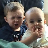 Un bébé mord le doigt d'un jeune garçon qui porte la main à sa bouche.