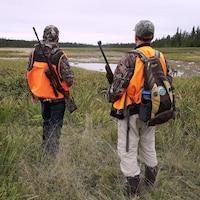 Des chasseurs se trouvent dans une clairière.