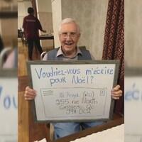 Un aîné tient une affiche sur laquelle il invite la population à lui écrire pour Noël.