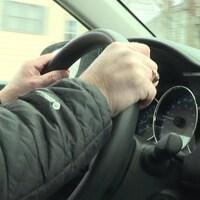 Les mains d'un homme sur le volant d'une voiture.