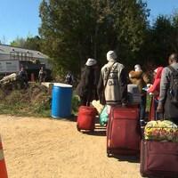 Des migrants se rendent au Canada par le chemin Roxham alors que des agents de la GRC les attendent de l'autre côté de la frontière.