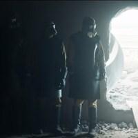 Trois personnes, dans les décombres d'une explosion nucléaire, avec un masque à gaz.