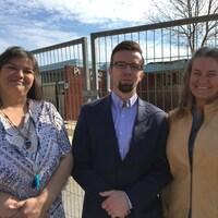 Trois personnes posant devant une clôture entourant une école.