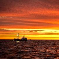 Un bateau de pêche devant l'horizon.