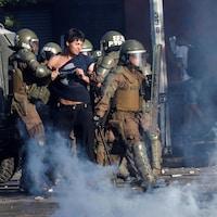 Des forces de sécurité interpellent un manifestant dans la rue.