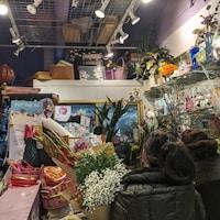 Dans la boutique, deux clientes avec des bouquets d'arrangements floraux dans les mains.