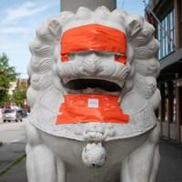 Une statue de lion recouverte de ruban adhésif orange.
