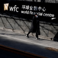 Une femme portant un masque passe devant un panneau indiquant World financial center.