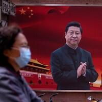 Une femme portant un masque protecteur aperçue dans une rue de Shanghai en passant devant un portrait géant du président chinois Xi Jinping.