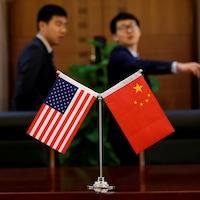 Les drapeaux des États-Unis et de la Chine installés sur une table de conférence.
