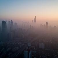 Une ville dont les bâtiments sont embrumés en raison de la pollution est vue de haut et de loin lors du lever du soleil.