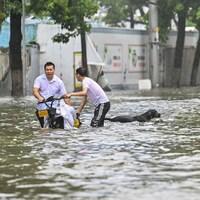 Des personnes et un chien pataugent dans une rue inondée.
