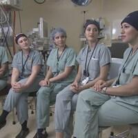 Cinq résidentes en chirurgie sont assises, habillées de leur blouse de médecin.