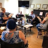 Des membres d'une chorale et leurs instruments de musique dans un salon.