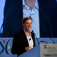 Une photo de Chris Hughes en train de donner un discours devant un écran géant rediffusant son image.