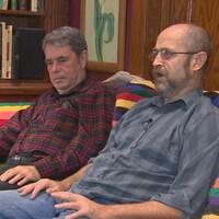 Deux hommes sont assis sur un divan côte à côte.