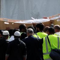 Des gens tiennent un cercueil à bout de bras.