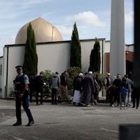 Un policier armé devant quelques fidèles à l'extérieur d'une mosquée