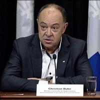 Christian Dubé, lors d'une conférence de presse, est assis derrière une table. Il parle dans un micro.