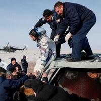 Christina Koch sort de la capsule avec l'assistance d'employés de Roskosmos.