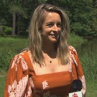 Une dame répond aux questions devant un micro de Radio-Canada. Des arbres et un lac se situent derrière elle.