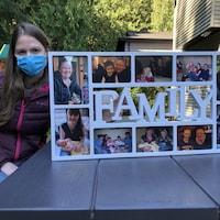 Christine Hutchins pose avec un cadre rempli de photos de famille, dont la photo de sa défunte sœur, Anne-Marie.