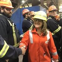 Une femme en uniforme de travail serre la main d'un homme devant un groupe de travailleurs