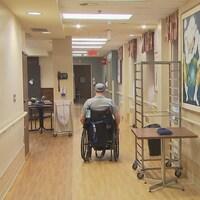 Une personne se déplace en fauteuil roulant dans un corridor du centre d'hébergement