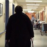 Une résidente marche dans le couloir d'un CHSLD.