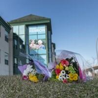 Trois bouquets de fleurs déposés sur l'herbe devant un CHSLD.