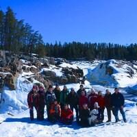 Un groupe de personnes devant des chutes, en hiver.