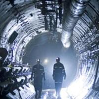 Deux hommes marchent dans un tunnel peu éclairé.