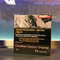Un emballage de cigarettes neutre, dont 80 % est recouvert d'un avertissement montrant un mourant. Une fine bande brune apparaît au bas du paquet, avec les inscriptions de la marque et du nombre de cigarettes qu'il renferme.