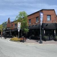 Un bâtiment en coin de rue abritant un restaurant et un cinéma.