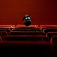 Un homme, portant un masque noir, est assis dans une salle de cinéma.
