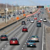 Des cônes orange bordent le long d'une autoroute.