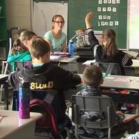 Des élèves dans une classe, dont une lève la main pour s'adresser à l'enseignante en avant.