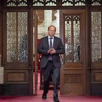 Claude Carignan marche à l'extérieur du Sénat.